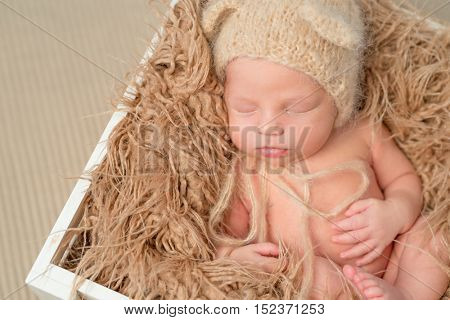 lovely newborn baby in knitted hat sleeping in wooden box with fluffy blanket