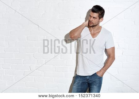 Portrait of a serious young man standing against white brick wall. Space for text.