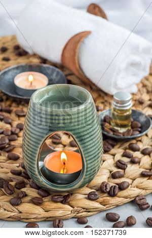 Aroma lamp with coffee essential oil on woven mat spa background vertical