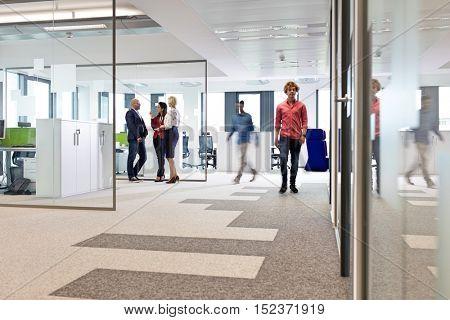 Businessmen and businesswomen in office corridor