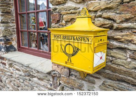 Marksburg Germany - May 23 2016: Retro yellow public post mailbox on a wall in Marksburg Braubach Germany.