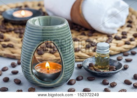 Aroma lamp with coffee essential oil on woven mat spa background horizontal