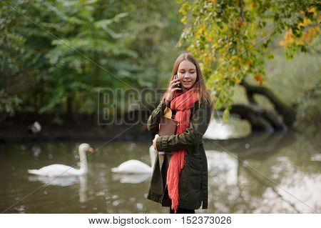 Autumn. Cute girl in a bright red scarf walking in autumn Park. Swans swim in the pond. Autumn trees are reflected in water. Girl talking on cell phone. She smiles.