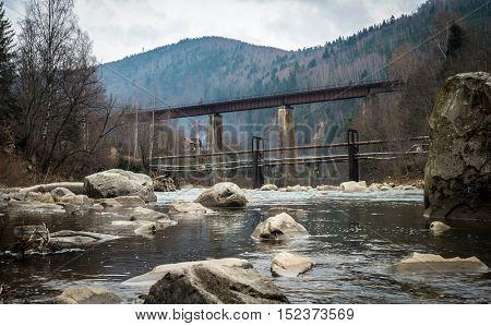 landscape in Carpathian mountains with river, railway bridge