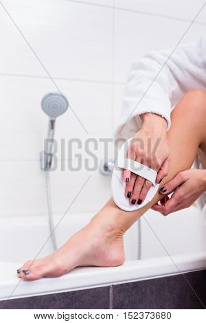 Woman sitting at edge of bathtub in bathroom and  applies peeling at her legs