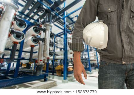Engineering and safety helmet standing on the details of the food manufacturing industry, water purification station.