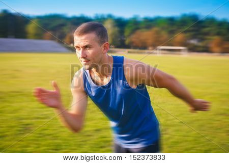 Young handsome sportsman running outdoors. Fit sporty man is at outdoor stadium.