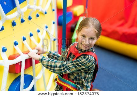 cute little girl on climbing wall with nets in entertainment center