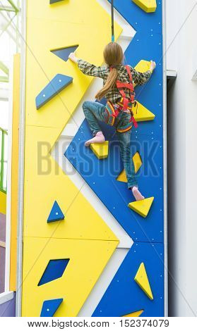little girl hanging on climbing wall in entertainment center