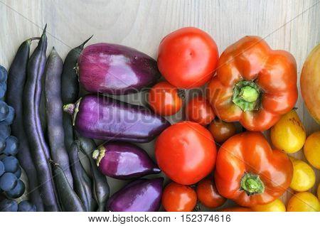 Autumn food background. Purple Beans grapes tomatoes peppers on light wooden surface. Top view.