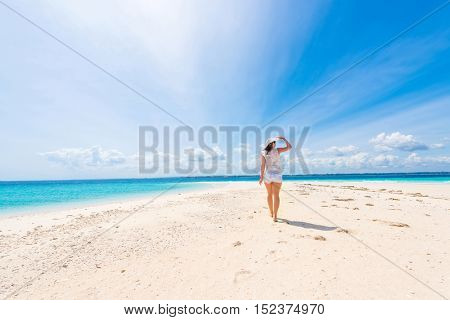 beautiful smiling girl in hat on a beach of blue ocean and sky on the background