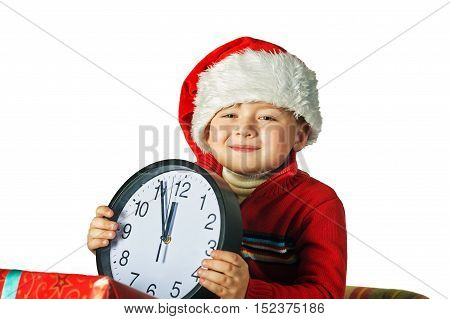 Beautiful little boy in red cap of Santa Claus with clock isolated on white background