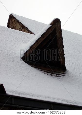 French farmhouse in the winter with snow covering the roof and triangular window