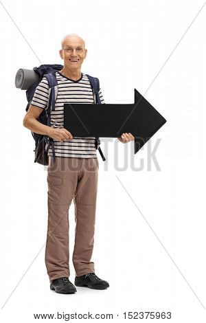 Full length portrait of an elderly male hiker holding an arrow pointing right isolated on white background