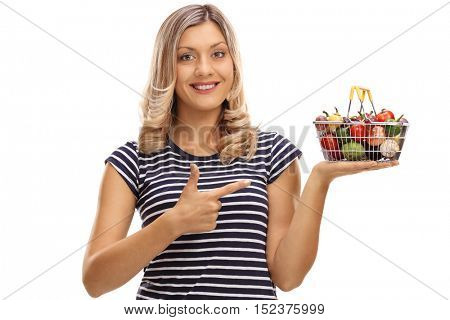 Joyful woman holding a small shopping basket full of fruits and vegetables and pointing isolated on white background