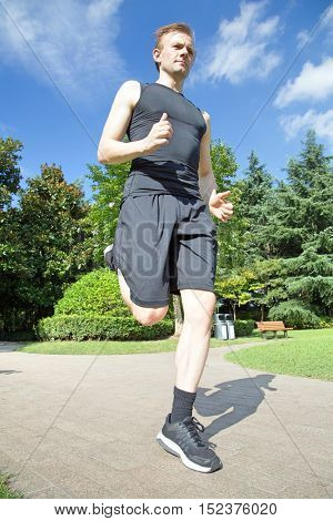 Low angle front  view of caucasian man running in park
