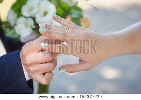 groom wears bride a wedding ring on the finger.