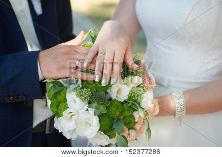 hands of bride and groom with gold rings on wedding bouquet.