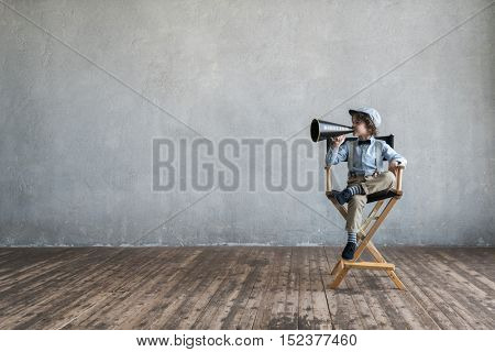 Little director on a chair in studio