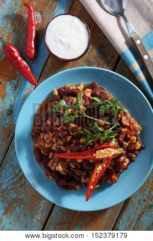 Chili con carne and red chili peppers on a rustic table