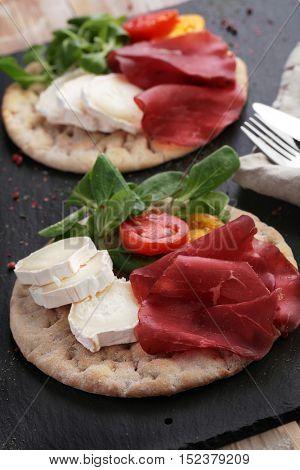 Swedish flatbread hallakaka with sliced ham, Sainte Maure cheese, tomato and lettuce