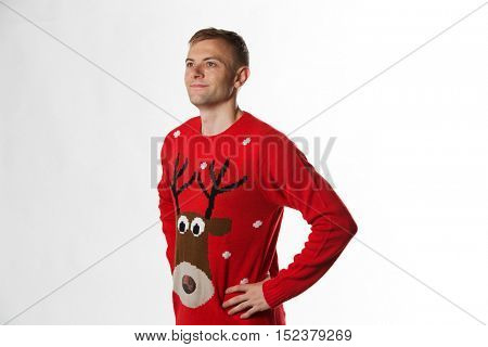 Caucasian man with hand on hips whilst wearing a christmas jumper looking away from camera