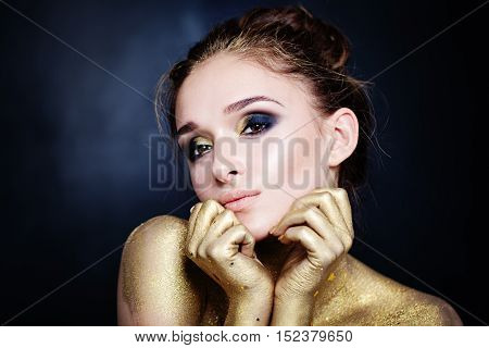 Glamorous Woman with Golden Makeup on Blue Background