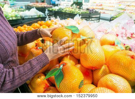 Woman buying fresh fruit at the supermarket