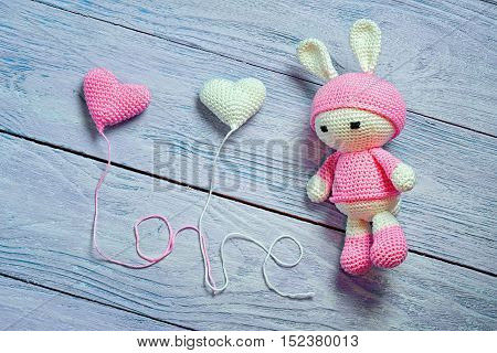 Handmade crochet rabbit toy with two heart balls and the word