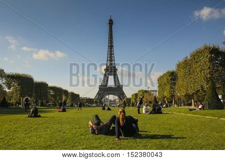 A beautiful weekend in Paris, relaxing on the green grass on Champ du Mars, with a great view of the Eiffel tower.