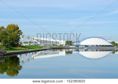 MINSK BELARUS - OCTOBER 1 2016: View of Palace of Sports and indoor ice skating rink on waterfront of River Svisloch. Unidentified people are strolling along promenade on sunny autumn day