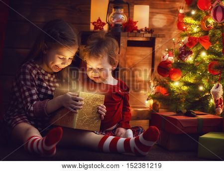 Merry Christmas and Happy Holiday! Two cute little children girls sisters with magic gift box on Christmas.