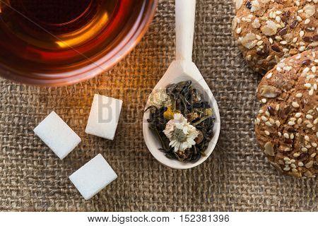 Herbal tea herbs and cookies on table