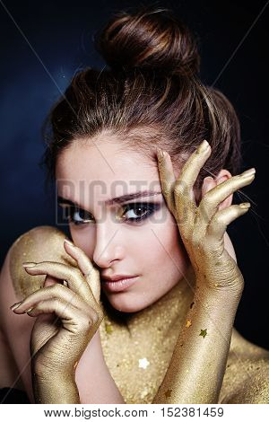 Pretty Model Woman with Golden Skin with Stars and Glamorous Makeup. Face closeup