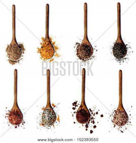 Collection of Various Spices in Wooden Spoons: Coriander Curry Powder Salt with Herbs Thyme Salt with Cayenne Pepper Salt with Petals Dried Paprika and Salt with Chili isolated on White background