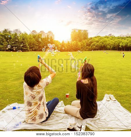 Two girls blowing soap bubbles on the park lawn in Shanghai.