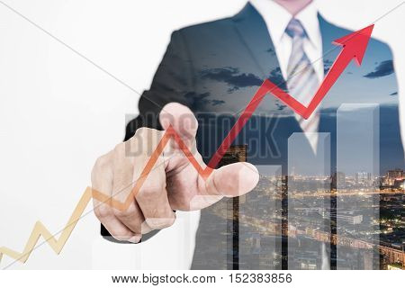 Businessman drawing a rising up arrow by finger, representing business growth