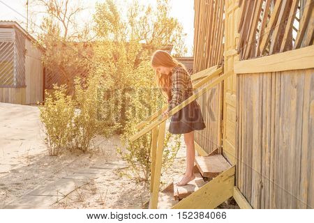 smiling little girl standing on wooden stairs barefoot on porch of cabin