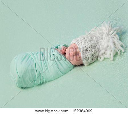 beautiful asleep newborn baby in big knitted hat