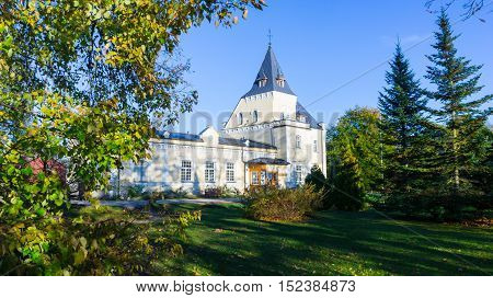 beautiful estate in autumn park, white house against a blue sky