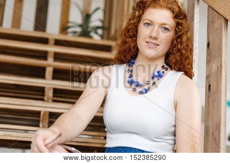 Portrait of young woman sitting at the stairs in office
