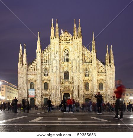Milan Cathedral (Duomo di Milano) in Milan at night, Italy (people in motion blur)