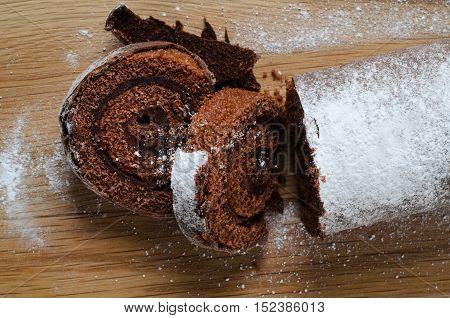 Chocolate Christmas Yule Log With Snowy Sprinkles On Wood