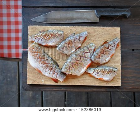 The process of preparation of river fish on a rustic kitchen. Peppered salted and incised chub and roach on the wooden surface on a dark table.