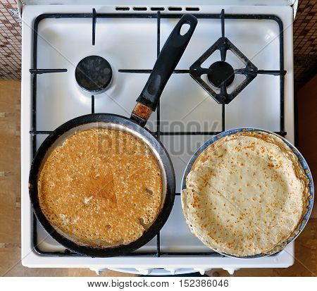 The process of making pancakes. Kitchen stove with a frying pan and a plate with thin pancakes. View from above.