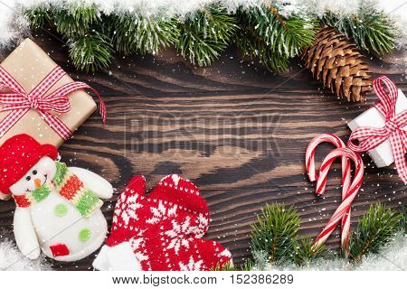 Christmas wooden background with gift boxes, decoration and snow pine tree. Top view with copy space for your text