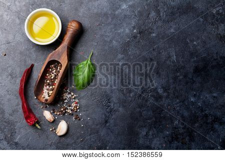 Herbs and spices. Cooking ingredients. Chili, basil, olive oil, salt and pepper. Top view over stone table with copy space for your recipe