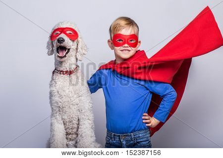 Handsome little superman with dog. Superhero. Halloween. Studio portrait over white background
