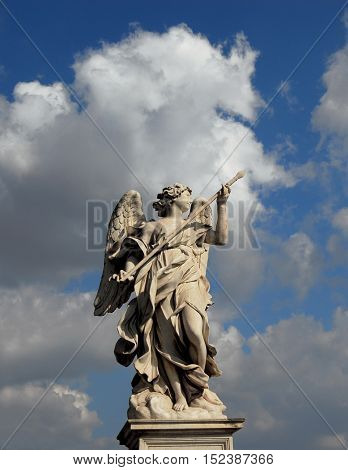 Beautiful angel statue holding a lance with heavenly sky from Sant'Angelo Bridge in the historic center of Rome (17th century)