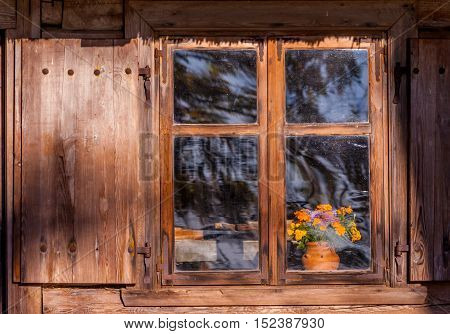 wooden window of an old house with shutters made of wood, on the windowsill is clay vase with autumn orange flowers, sunlit window, a photo from the outside, from the street, autumn atmosphere,October